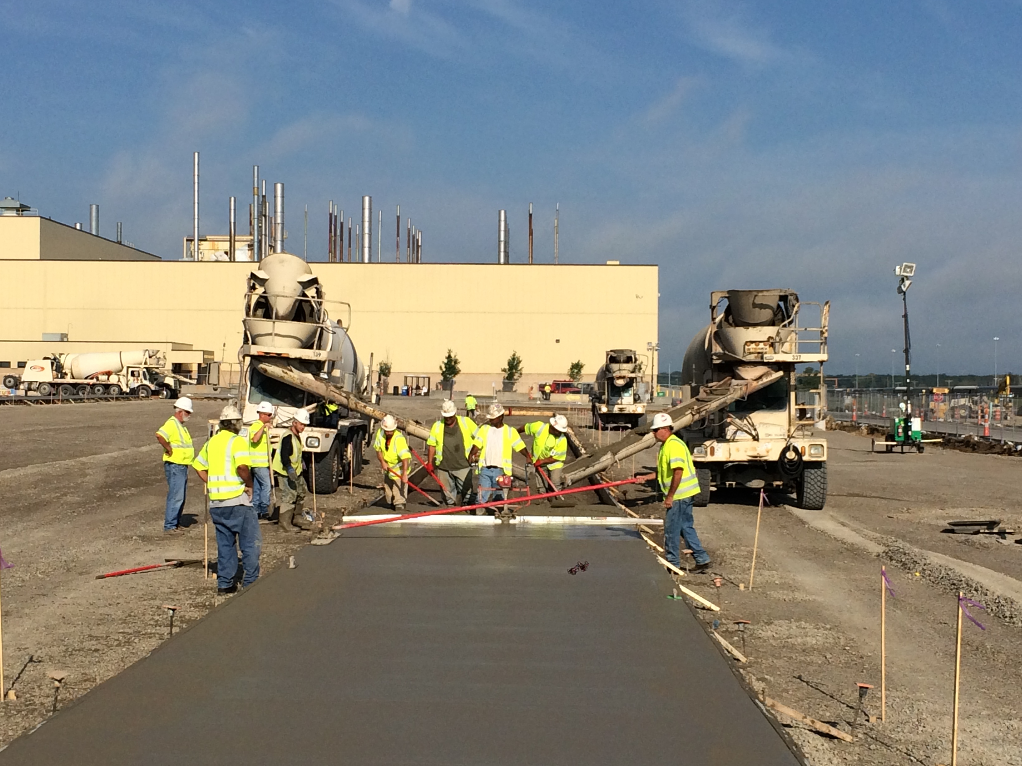 Workers paving concrete at Honda